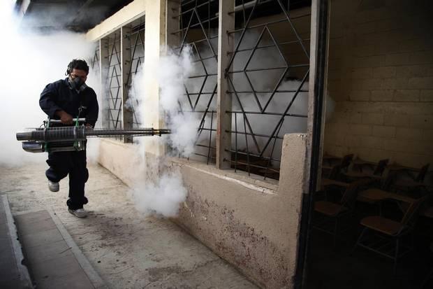 A city worker fumigates a public school against mosquitoes in Tegucigalpa, Honduras.