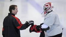 Canada's goaltending coach Ron Tugnutt, (left) from Peterborough, Ont., talks with goalie Malcolm Subban, from Toronto, during practice for the World Juniors team in Calgary on Saturday Dec. 15, 2012. (Larry MacDougal/THE CANADIAN PRESS)