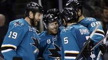 San Jose Sharks' Joe Pavelski (8) is hugged by teammates after scoring against the Toronto Maple Leafs during the third period of an NHL hockey game Tuesday, March 11, 2014, in San Jose, Calif. San Jose won 6-2. (Associated PRess)