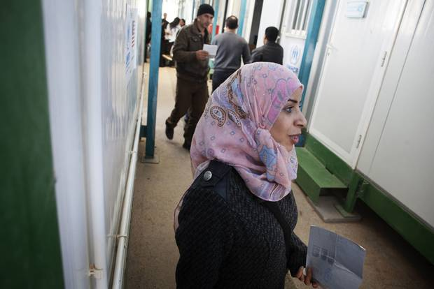 Saja, a mother of three, holds her refugee application in her hand but is leaving the screening centre dejected. She received a 3 rating, meaning a decision has been deferred because her husband is not present in Jordan.