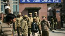 Delhi policemen stand guard near the gate of a district court where the accused in the gang rape and murder of a 23-year-old student are undergoing trial on Jan. 24, 2013. The trial of the five men charged began in a closed courtroom Thursday with opening arguments by the prosecution lawyers in a special fast-track court set up just weeks ago to handle sexual assault cases. (Altaf Qadri/AP)