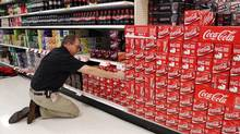 An employee arranges cartons of Coca-Cola at a store in Alexandria, Va., in this file photo. (KEVIN LAMARQUE/REUTERS)