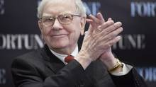 Billionaire investor Warren Buffett applauds during a seminar in Omaha, Neb. May 1, 2013. (Nati Harnik/THE CANADIAN PRESS)