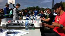 Vancouver Canucks goalie Roberto Luongo and twins Henrik and Daniel Sedin playing table hockey with residents of Haida Gwaii during a team visit and lunchtime barbeque at the community hall in Old Massett on Tuesday. (David Ebner/The Globe and Mail)
