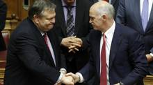 Greek Finance Minister Evangelos Venizelos, left, shakes hands with Prime Minister George Papandreou. (Yiorgos Karahalis/Reuters/Yiorgos Karahalis/Reuters)
