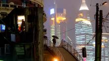 A Chinese woman (with umbrella) walks in between the new and old districts of Shanghai October 31, 2002. (GUANG NIU/REUTERS)