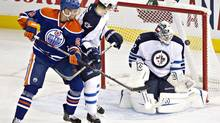 Winnipeg Jets goalie Edward Pasquale (32) makes the save as Jacob Trouba (3) and Edmonton Oilers Jesse Joensuu (6) battle in front during second period NHL preseason hockey action in Edmonton, Alta., on Monday September 23, 2013. (JASON FRANSON/THE CANADIAN PRESS)
