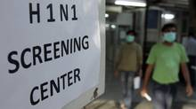 People wearing surgical masks walk out of a H1N1 flu screening centre in Ram Manohar Lohia hospital in New Delhi. (FAYAZ KABLI)