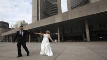 Marvin Mag-Iba, left, and his new bride Mutya Ella Vallada, right, leave Toronto City Hall after they joined the 40 couples to tie the knot on December 12, 2012 (12/12/12). (Michelle Siu For The Globe and Mail)
