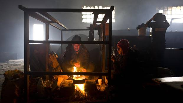 An Afghan refugee boils water on a fire to make tea in an abandoned warehouse where he and other migrants took refuge in Belgrade, Serbia.