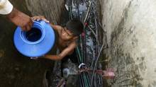 A boy collects water from a broken pipe in Mumbai, India. There is a need for water infrastructure in many places around the world. (Rafiq Maqbool/Associated Press)