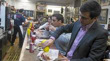 Mohsen Khlifi puts mustard on his smoked meat sandwich prepared at Schwartz's deli on St. Laurent in Montreal (Christinne Muschi/Reuters)