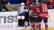 Team Canada forward Jonathan Drouin (29) takes out Team USA forward Ryan Hartman, left, into the Canada bench during first period IIHF World Junior Championships hockey action in Ufa, Russia, Dec. 30, 2012. \ (Nathan Denette/THE CANADIAN PRESS)