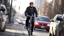 Gil Penalosa bikes along a busy street in Toronto. (Moe Doiron/The Globe and Mail)