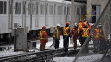 Toronto Transit Commission workers inspect the rail line after a train stopped in the morning rush hour just outside of Kipling Station in Etobicoke. (Deborah Baic/The Globe and Mail)