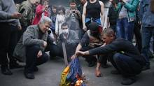 Pro-Russia protesters burn a Ukranian flag outside the district council building in Donetsk, eastern Ukraine May 4, 2014. (MARKO DJURICA/REUTERS)