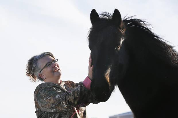 Sandra McLeod with her horses at feeding time on her ranch near Sylvan Lake, Alta.
