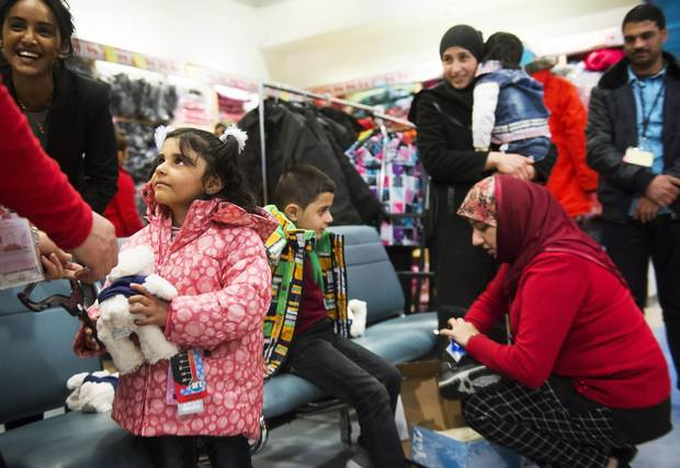 Syrian refugees get new winter clothing at Pearson International Airport in Toronto Feb. 29, 2016.