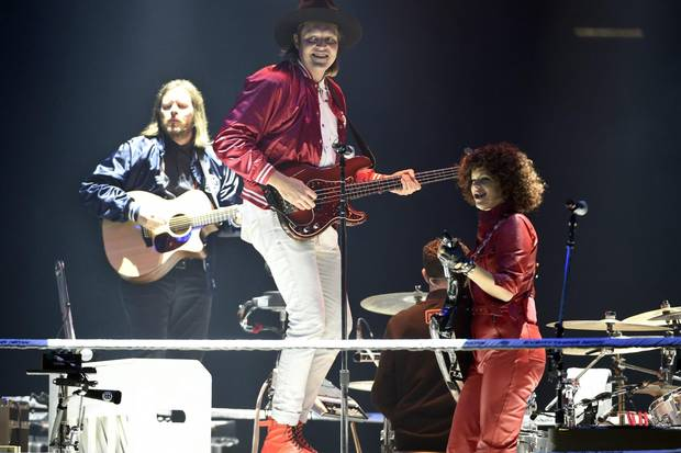 Left to right: Tim Kingsbury, Win Butler and Regine Chassagne of Arcade Fire perform in Inglewood, Calif., on Oct. 20, 2017.