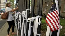 "woman ties a ""Ribbon of Remembrance"" onto the fence at St. Paul's Chapel on September 8, 2011 in New York City. (Tama/Getty Images)"