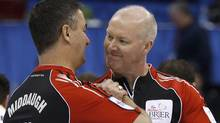 Ontario skip Glenn Howard, right, celebrates his teams win with third Wayne Middaugh following an evening page playoff draw against Manitoba at the Tim Hortons Brier in Saskatoon, Sask. Friday, March, 9, 2012. THE CANADIAN PRESS/Jonathan Hayward (Jonathan Hayward/CP)