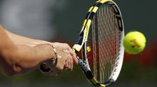 A close up of the racquet and ball as Caroline Wozniacki of Denmark returns a shot against Vania King of the U.S. during their match at the Indian Wells WTA tennis tournament in Indian Wells, California, March 12, 2010. (DANNY MOLOSHOK/REUTERS)