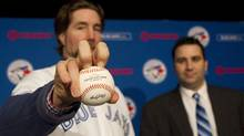 Pitcher R.A. Dickey (left) stands with Toronto Blue Jays general manager Alex Anthopoulos as he demonstrates his knuckleball grip following a news conference in Toronto on Tuesday January 8, 2013 as the Jays introduce the newest addition to their roster. (Chris Young/The Canadian Press)