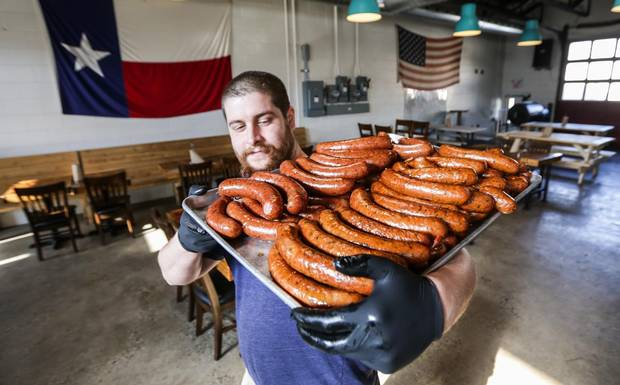 Pit cook Matthew Pelechaty carries in a cooking sheet full of sausage fresh out of the big smoker at Adamson Barbecue in North York, Toronto.