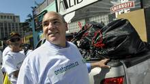 Deputy premier George Smitherman helps clean up garbage on July 14 as part of a new volunteer effort during the Toronto strike. (Fred Lum/The Globe and Mail)