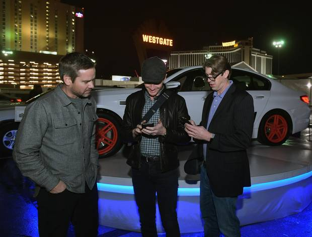 Senior Director of Product, Self-Driving at Lyft, Taggart Matthiesen (L) watches as actor Neil Patrick Harris orders a Lyft and Aptiv self-driving car through the Lyft app during CES 2018 at the Las Vegas Convention Center on January 8, 2018 in Las Vegas, Nevada.