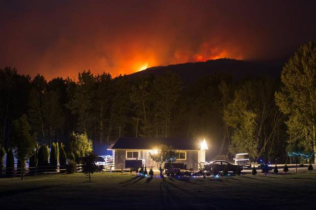 A wildfire burns on a mountain behind a home in Cache Creek, B.C., in the early morning hours of July 8.