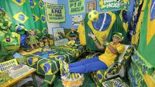 Brazilian soccer fan Marilza Guimaraes da Silva, 63, plays with a ball as she poses for picture, dressed in one of her many outfits matching the colors of the Brazil's national flag (green, yellow, white and blue) at her home in Brasilia May 27, 2014. (STRINGER/BRAZIL/REUTERS)