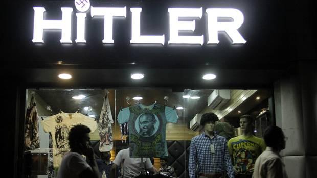 Indians walk past a shop named