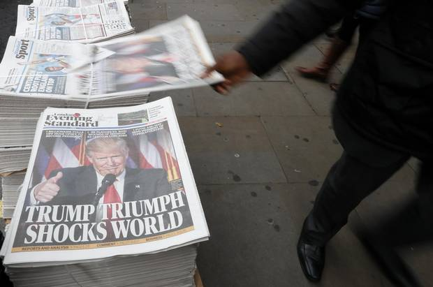 A passerby takes a copy of the Evening Standard in London on Nov. 9, 2016.