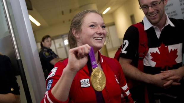 Gold medalist Rosie MacLennan shows her medal as she arrives to a crowd of supporters at Toronto's Pearson Airport Aug. 13, 2012.