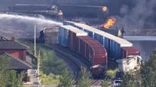 A tanker continues to burn as fire fighters douse rail containers in downtown Lac Mégantic, Quebec early July 7, 2013 a day after a train carrying crude oil tankers derailed and burst into flames. (Moe Doiron/The Globe and Mail) (Moe Doiron/The Globe and Mail)
