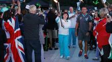 Welsh torchbearer Marsha Wiseman carries the Paralympic flame into Stoke Mandeville Stadium during the torch relay ceremony in Buckinghamshire August 28, 2012. (OLIVIA HARRIS/Reuters)