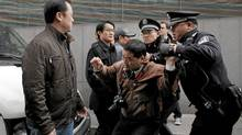 "A man (2nd R) is arrested by police after calls for a ""Jasmine Revolution"" protest, organised through the internet, in front of the Peace Cinema in downtown Shanghai February 27, 2011. (© Carlos Barria / Reuters/Carlos Barria/Reuters)"