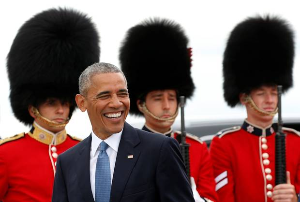 U.S. President Barack Obama smiles as he walks past an honor guard upon arrival to attend the North American Leaders' Summit in Ottawa.