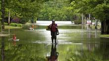 A Quebec man sloshes through the flooded streets of St-Jean on May 27, 2011. (Ruan Remiorz/The Canadian Press/Ruan Remiorz/The Canadian Press)