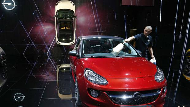 An employee polishes the windshield of an Opel Adam S during media day, ahead of the 84th Geneva Motor Show. (ARND WIEGMANN/REUTERS)
