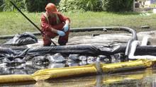 The Wisconsin spill occurred almost exactly two years after a spill fouled parts of the Kalamazoo River in Michigan. In this July 29, 2010, file photo, a worker monitors water in a nearby creek affected by the 2010 spill. (Paul Sancya/AP)