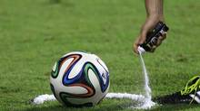 In this June 6, 2014, photo, a referee uses vanishing spray during a referee's training session in Rio de Janeiro, Brazil. Referees will use vanishing spray during 2014 World Cup to stop defensive walls creeping forward at free-kicks. (Hassan Ammar/AP)