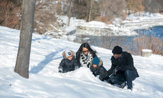 Andre and Sunshine Batson and their three and half year old twins Maxwell (grey hat) and Brandon (blue hat) enjoy their New Years Day in the snow covered Lakeside Park near their home in Oakville.