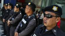 Police officers stand guard at a shopping mall in Bangkok on June 8, 2014. Thailand's junta prepared a force of over 6,000 troops and police for deployment in Bangkok on Sunday to smother protests and prevent opposition to the May 22 coup from gaining momentum. (ATHIT PERAWONGMETHA/REUTERS)