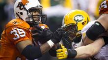 In this file photo, Greg Peach of the Edmonton Eskimos tries to take down B.C. Lions Tim Brownduring during the first quarter of CFL action in Vancouver November 20, 2011. On Thursday, The Bombers announced they had signed import defensive end Greg Peach and then confirmed he will play in Sunday's game against Saskatchewan. (JOHN LEHMANN/The Globe and Mail)