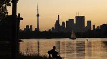 A man sits on a bench in front of the Toronto skyline. (MARK BLINCH/REUTERS)