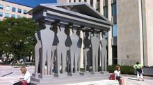 """People relax beside the Edwina Sandys sculpture """"Pillars of Justice"""" outside the court house at 361 University Avenue in Toronto in this October, 2012 photo. (Randall Moore/The Globe and Mail)"""