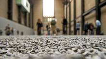 "Members of the media walk on ceramic seeds, during the launch of Chinese artist Ai Weiwei's ""Sunflower Seeds"" at the Tate Modern in south London, on October 11, 2010. (LEON NEAL/LEON NEAL / AFP/Getty Images)"