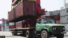 A crane loads a container onto a truck at a port in Qingdao, Shandong province, on May 10, 2012. (CHINA DAILY/REUTERS)